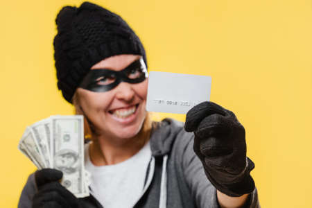 A female hacker wearing a black hat and a mask-glasses, smiling maliciously and holding a wad of money and a bank credit card. Yellow background. The concept of theft and cybercrime.