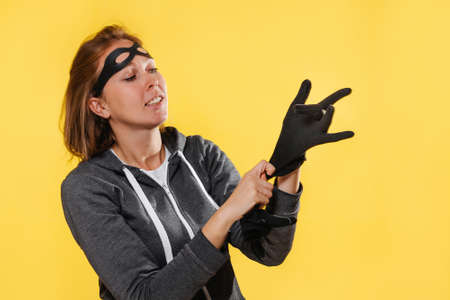 Portrait of female robber in a mask, wearing gloves. Yellow background. The concept of crime.