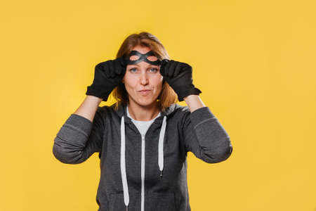 A female robber wearing gloves, puts a mask over her eyes. Yellow background. The concept of crime.