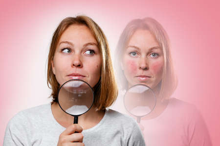 Portrait of a young woman with a magnifying glass near her face. In the background is a semi-transparent portrait of a woman with rosacea on her cheeks. Rosacea Treatment Concept.