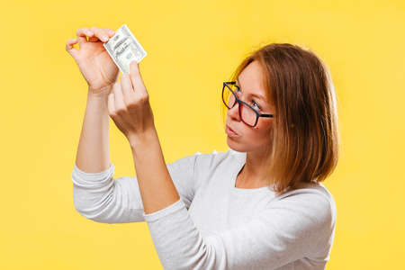 A pensive woman looking at the dollar bill checking for falsity. Yellow background. The concept of checking counterfeit money. Imagens
