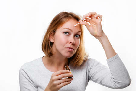 Portrait of a young woman smearing medicine on a pimple on her forehead. White background. Acne and pimples.