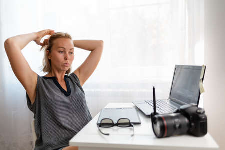 Office work, freelance and business. The young woman thought, working at her laptop. On the table are the camera, glasses, laptop and tablet.