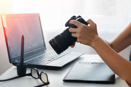 Business and creativity. Women's hands holding the camera. Nearby is a laptop, tablet and stylus. Close up. Stock fotó