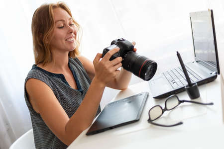A young woman photographer sitting at his Desk and working with a camera. Close up.
