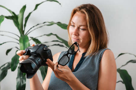 Office. Portrait of a young woman holding glasses and looking into the camera. Freelance and creative work. Imagens