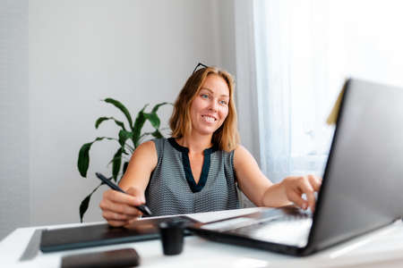 Portrait of a smiling young woman drawing on a tablet and working on a laptop. Freelance and creative work.