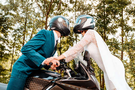 Wedding, newlyweds. A man and a woman in wedding dresses and motorcycle helmets are attracted to each other. A man is sitting on a motorcycle, and a woman is standing in front of him. Side view. Close up. Stock fotó