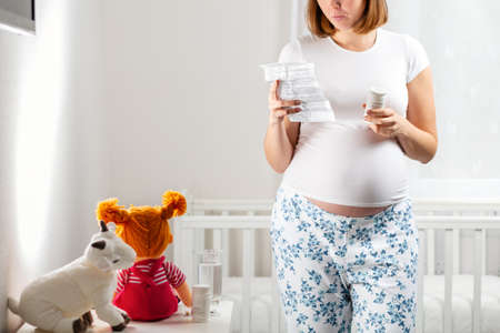 A young pregnant woman holds tablets in her hands and reads the instructions for using the medicine. Baby cradle in the background. Concept of pregnant women's health. Close up. Stock fotó