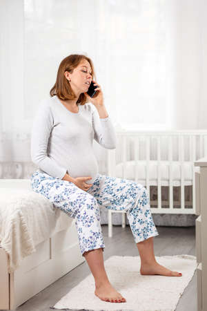 A young pregnant woman is sitting on a bed in the nursery, chatting on her smartphone. Concept of modern technologies and pregnancy