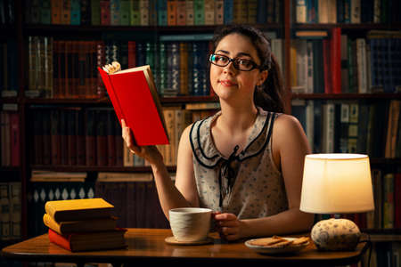 Quarantine. A young Caucasian woman with glasses is reading a book at the table, holding a Cup of tea. The home library is in the background. The concept of self-isolation, distance learning and remote work.