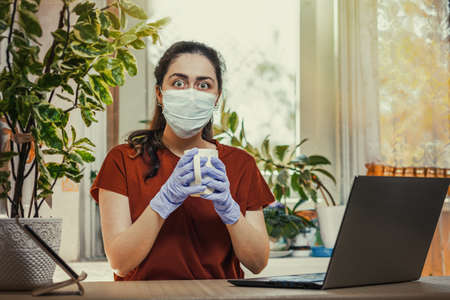 Freelance.A young Caucasian woman in gloves and a medical mask, holding a Cup of tea, and her eyes bulged. Home office, laptop on the table.Concept of quarantine, self-isolation and coronovirus.