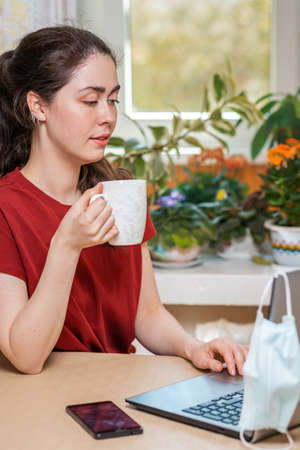 A young woman holding a Cup of tea and working at a laptop, on which hangs a medical mask, and next to the table is a smartphone. Concept of self-isolation and protection from coronovirus.