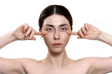 Beauty and skin care. Portrait of a young beautiful Caucasian woman pointing her fingers under the eye area. White background. The concept of lifting procedures against the first signs of skin aging. Stock fotó