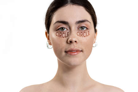 Portrait of a young beautiful woman, with dark circles under her eyes, schematic text. White background. Copy space. The concept of dark circles under the eyes.