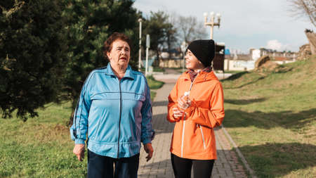 Portraits of talking grandmother and her adult granddaughter walking on the street. Outdoor. International Day of Older Persons.
