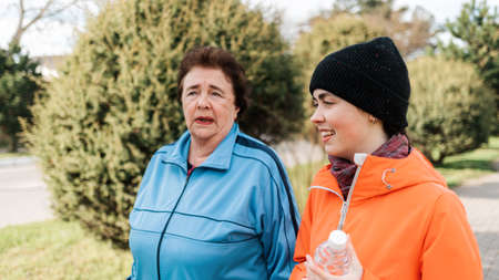 International Day of Older Persons. Portraits of a grandmother with an adult granddaughter walking in the park and talking. Family walks in the park.