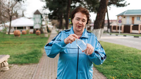Concept of International Day of Older Persons. Portrait of an elderly smiling woman in a tracksuit opening a bottle of water. Outdoor activity. Imagens