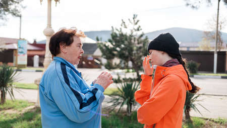 Grandmother scolds the adult granddaughter, standing on the street. Negative communication and problems in the family. Side view.