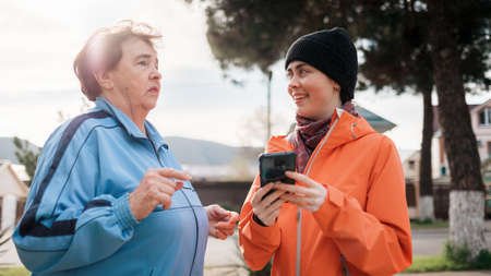 Portrait of a smiling elderly and young woman with a phone in her hand. Family walks in the open air. Communication concept.