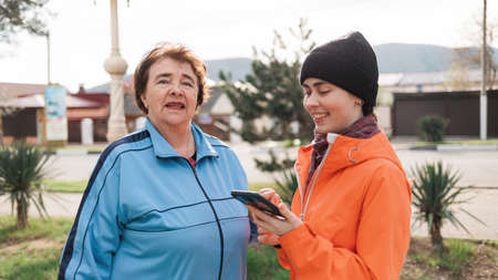 Portrait of a smiling elderly and young woman with a phone in her hand. Family walks in the open air. Online map concept. Imagens