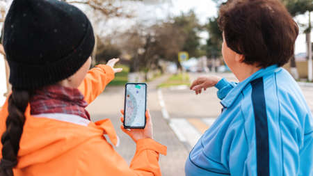 A young woman holds a smartphone with an online map and shows the way to an elderly woman with her hand. Mature woman was lost in the city. Concept of memory loss and dementia.