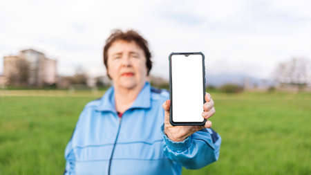Portrait of an elderly woman in a tracksuit, holding a smartphone with a white screen in her hand. Mock up. Outdoor. The concept of modern technologies for the elderly.