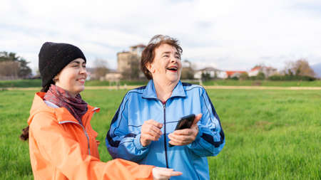 Portrait of a happy young and elderly women with a phone in her hand, looking away. Outdoor. International Day of Older Persons. Stock fotó