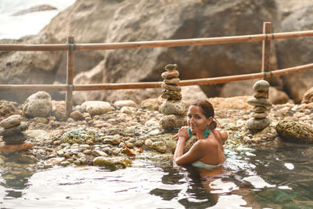 Caucasian girl with a smile bathes in the warm natural pool.