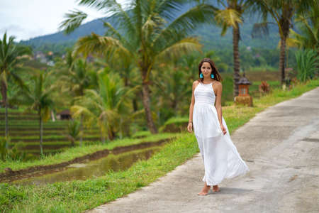 Beautiful tanned woman in white dress posing standing on the road. In the background are palm trees and other tropical vegetation.