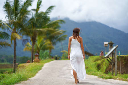 A tanned girl in a white dress walks forward on the road. The view from the back. In the background, a mountain in the fog and palm trees. Imagens