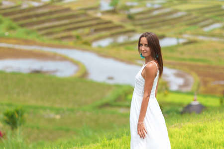 Tanned young woman posing on the background of rice fields. Close up
