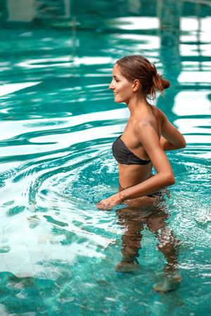 Tanned beautiful woman comes into the pool. Vertical.