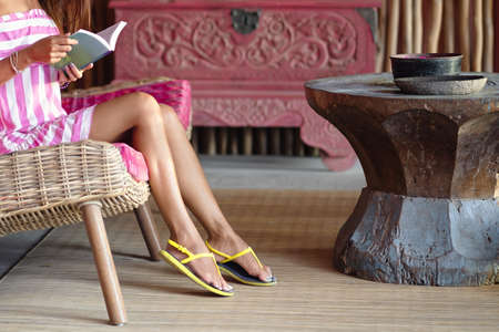 Slender foots of beautiful woman sitting on a pink sofa and reading a book. Interior in ethnic style. Close up.
