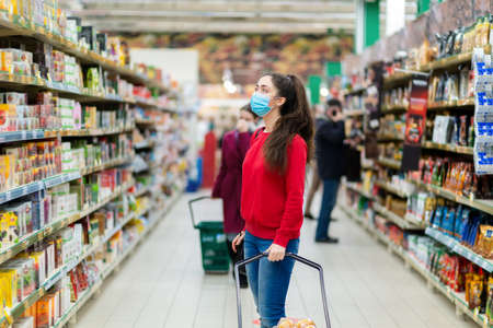 Shopping during the coronavirus pandemic. A young woman in a medical mask on her face looks at the windows with products in a supermarket. The concept of consumerism and the new reality.