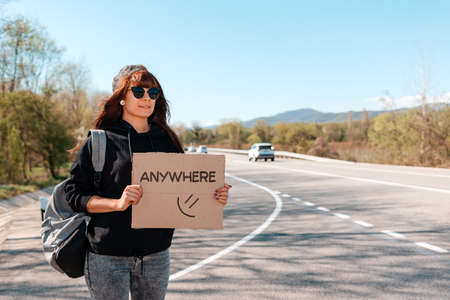 Smiling caucasian young woman in sunglasses and cap holding a cardboard sign with text anywhere. Copy space. The concept of local traveling and hitchhiking. 版權商用圖片