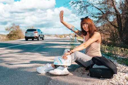 Concept of hitchhiking. Young woman in sunglasses sitting along the road with backpack and hitchhiking a car with hand. Local travel.