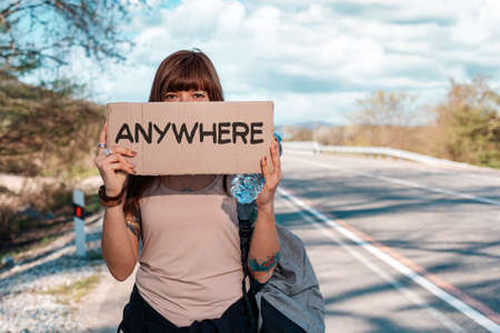 Young woman with tattoed hand holding a cardboard sign with text anywhere and cover her face. Outdoor. The concept of local traveling and hitchhiking.