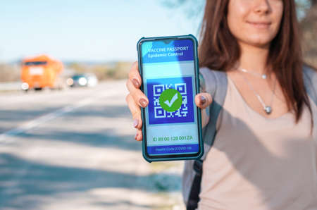 Digital health passport. Woman holding a smartphone with a negative test results for coronavirus. Close up. The concept of a new normal and travel during the pandemic.