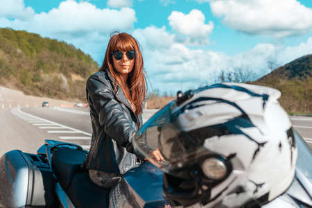 World Motorcyclist Day. A young caucasian woman in a leather jacket and sunglasses sitting on a motorbike. Road and cloudscape on the background. Motorcycle local travel concept.