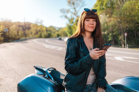 Motorcycle local travel. Portrait of smiling woman in a leather jacket and sunglasses sitting on a motorcycle and using a smartphone. World Motorcyclist Day concept. 版權商用圖片