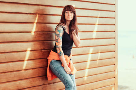 A young beautiful woman with tattoos on her arm, posing near a wooden wall.Outdoor.