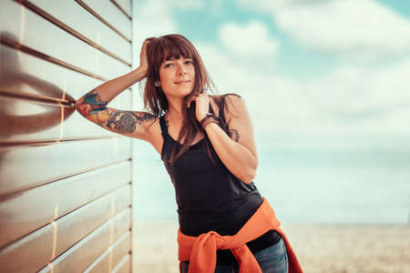 Young beautiful smiling woman with tattoos poses, leaning against a wooden wall. In the background, the sky with clouds and the sea. Copy space. 版權商用圖片