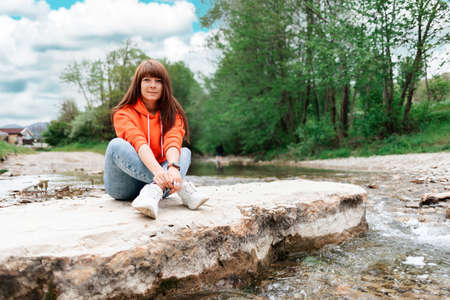 A young smiling woman sitting crossed legs on a rock on the river bank. Park and outdoor activities.
