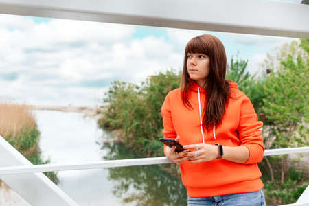 A young pretty woman holds a smartphone in her hands. Park and river in the background. The concept of smartphones and smart watches.