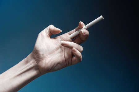 World No Tabacco day. A pale, crooked female hand, close-up, holding a new cigarette. Dark blue background. The concept of nicotine addiction. 版權商用圖片