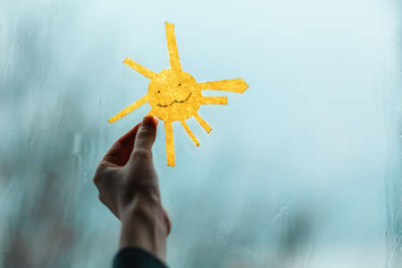 A child's hand holds the sun, cutted out of felt, against the window. Outside the window, rain and bad weather. Close-up. The concept of depression and good mood 版權商用圖片