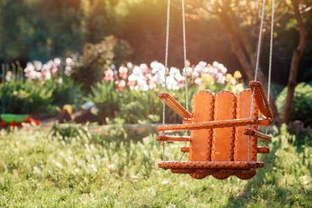 International Children's Day. Handmade wooden swing hanging in the kindergarten, on the summer sunny playground. Nobody. Family planning concept. 版權商用圖片