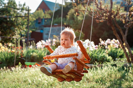 Happy Children's Day. Cute toddler with blonde hair having fun on a swing. Sunny backyard in the background. The concept of the International Children's Day.