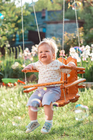 Smiling baby girl having fun on a swing. Sunny playground in the summer back yard. Vertical. The concept of the International Children's Day.